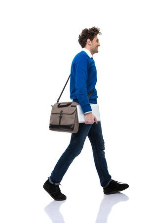 persona caminando: Hombre con el bolso que recorre m�s de fondo blanco Foto de archivo
