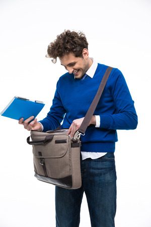 designer bag: Smiling young man standing with bag and notebook Stock Photo