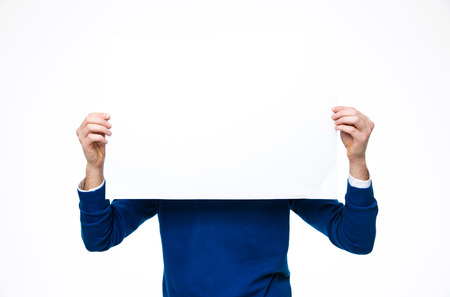 man holding sign: Man holding a blank paper over white background Stock Photo