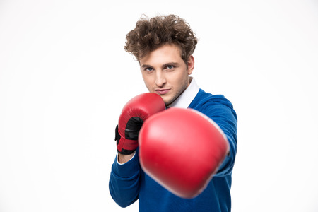 punching: Business man in boxing gloves punching at the camera