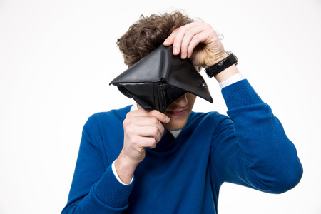 afflict: Young man looking through empty wallet at the camera