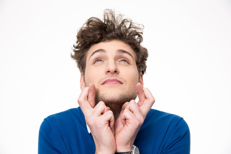 anticipate: Young handsome man with crossed fingers over white background