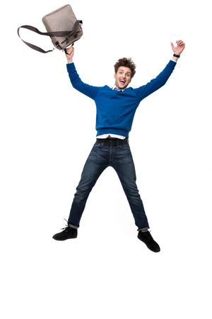 vertica: Laughing business man jumping with bag over white background