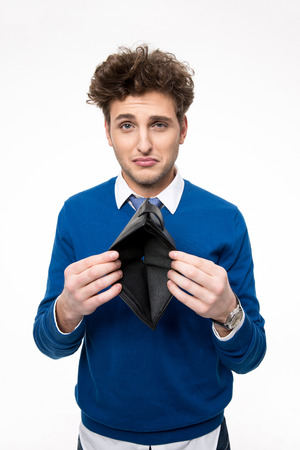 afflict: Upset young man holding emty wallet over white background Stock Photo