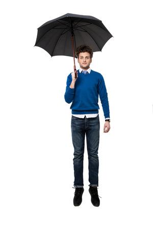 Handsome businessman standing under umbrella over white background photo