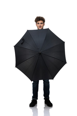 Young casual man holding an umbrella in front of him a photo