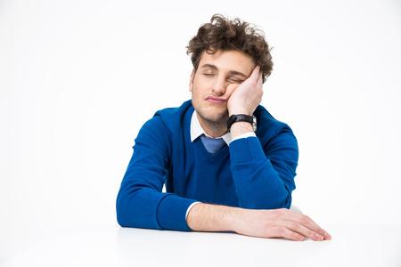 Unavený podnikatel spí u stolu nad bílým pozadím