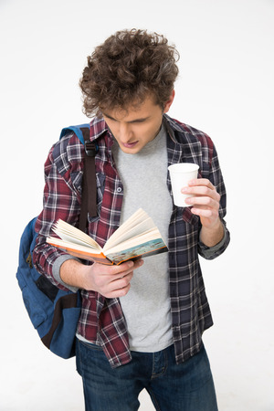 concetrated: Young male student standing with book and coffee
