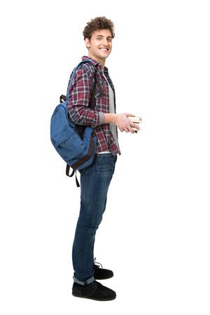 persona de pie: Retrato de cuerpo entero de un estudiante masculino feliz sobre fondo blanco