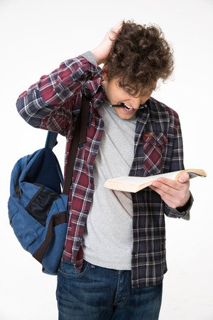 Male student biting pen and reading book over gray background photo