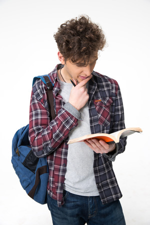 Portrait of a young man reading book over gray background photo
