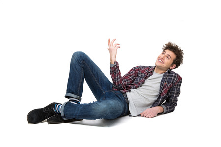 confortable: Happy thoughtful young man lying on the floor and looking up at copyspace