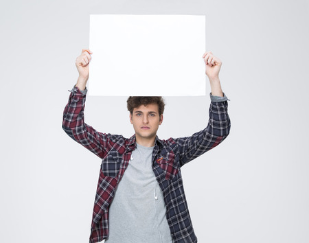 Junger Mann mit lockigen Haaren hält leere Plakatwand