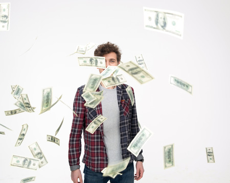 Casual man throwing Money Into Air over gray background Stock Photo