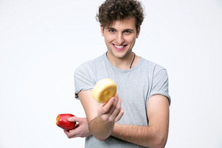 Happyman holding apple and donut over gray background photo