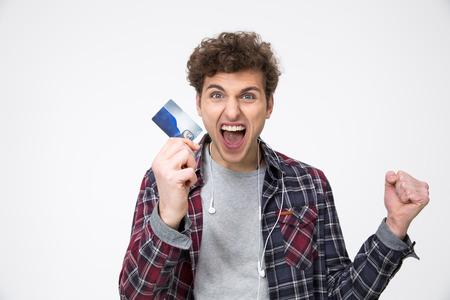 クレジット カードで立っていると叫んでいるカジュアルな男