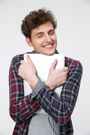 hugging: Happy man hugging laptop over gray background