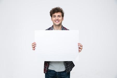 držení: Šťastný muž s kudrnatými vlasy drží prázdný billboard