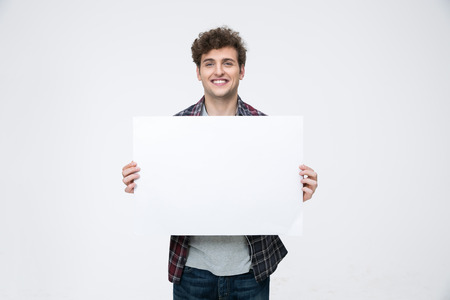 Happy man with curly hair holding blank billboard Foto de archivo