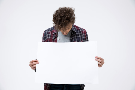 cartel: Young man holding blank billboard and looking on it Stock Photo
