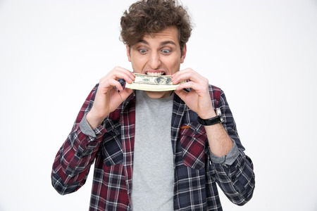 stingy: Young casual man biting money over gray background Stock Photo