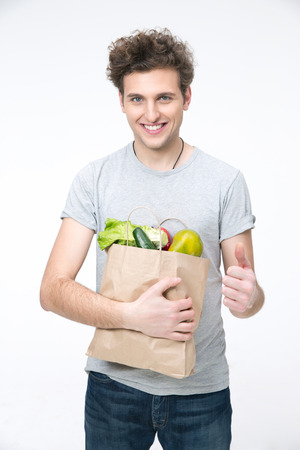 posing  agree: Happy man holding a bag of groceries and giving thumb up Stock Photo