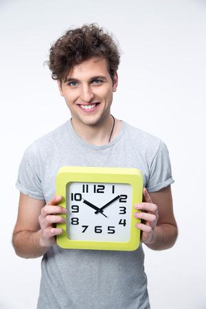 灰色の背景の上の大時計と幸せな男子生徒