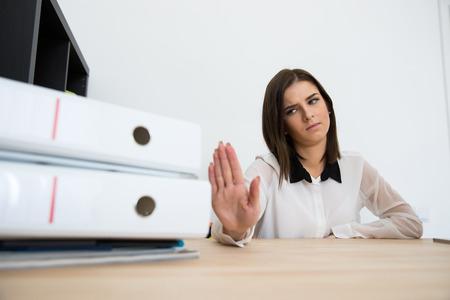acoso laboral: Joven empresaria sentado en la mesa y diciendo - No