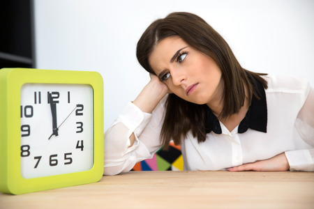 stress management: Businesswoman sitting at the table with clock. Waiting for break