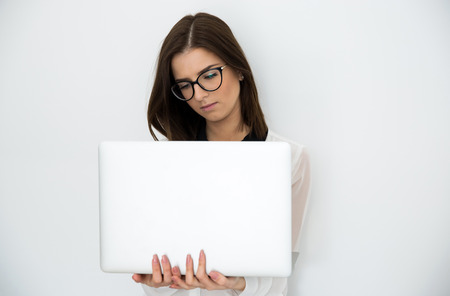 careerists: Young beautiful woman standing with laptop over gray background Stock Photo