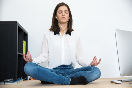 Young woman meditating at the table in office