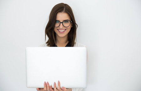 Attractive happy businesswoman standing with laptop over gray background Stock Photo