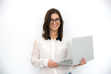Cheerful young businesswoman standing with laptop