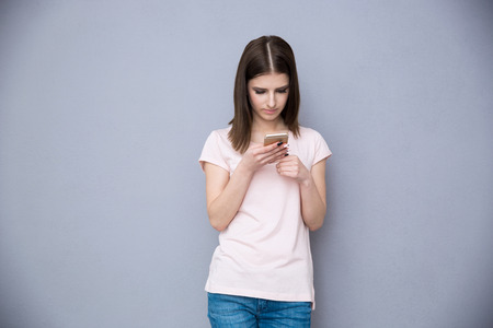 concetrated: Young woman using smartphone over gray background