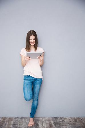ragazze a piedi nudi: Donna sorridente utilizzando il computer tablet e appoggiato al muro grigio