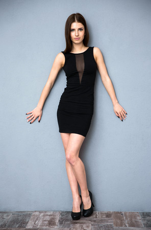 Full length portrait of a cute woman in hot dress leaning on the wall Standard-Bild