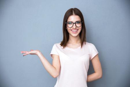 Feliz mujer joven con gafas que presenta algo en la mano