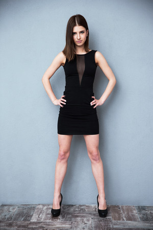 black dress: Full length portrait of a woman standing in hot dress