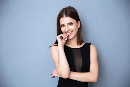 Portret van een glimlachende vrouw in hete jurk permanent over grijze achtergrond Stockfoto
