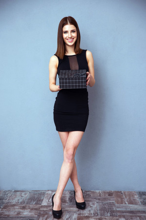 Full length portrait of a smiling woman holding gift photo