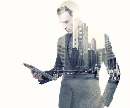 hombre de negocios: Doble exposición de un empresario y una ciudad con una tableta sobre fondo blanco Foto de archivo