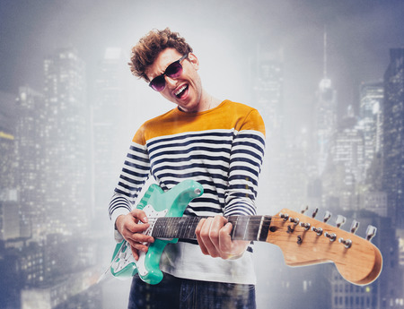 guitar background: Double exposure of a city and happy man playing guitar Stock Photo