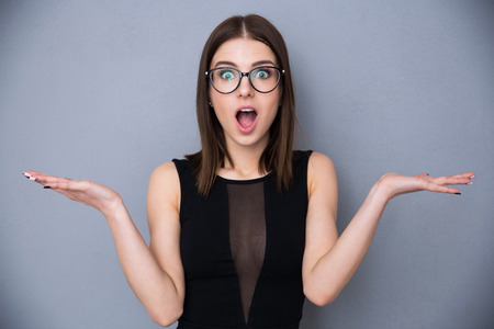 Young beautiful woman with facial expression of surprise standing over gray background. Wearing in trendy black dress and glasses. Looking at the camera Stockfoto