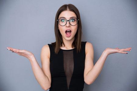 Mujer hermosa joven con la expresión facial de la sorpresa de pie sobre fondo gris. El uso de vestido negro de moda y gafas. Mirando a la cámara