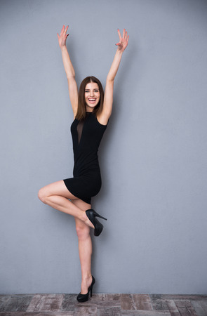 trendy: Full length portrait of a laughing cute woman in fashion black dress. Posing over gray background. With raised hands up. Looking at camera.