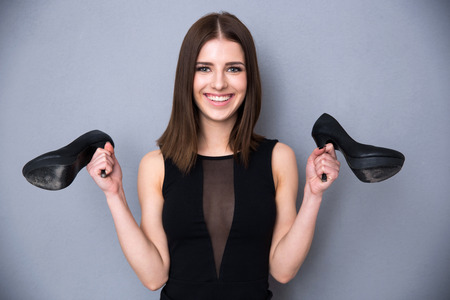 Portrait of a smiling young woman in fashion black dress holding shoes. Standing over gray background. Looking at camera. Stock Photo