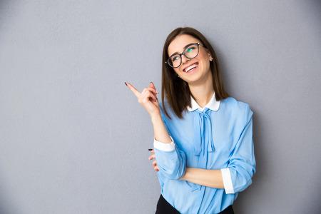 Femme d'affaires gai pointant loin sur fond gris. Portant une chemise bleue et des lunettes. En détournant les yeux Banque d'images - 38369546