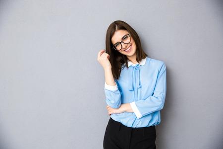 灰色の背景の上に立ってメガネの女性実業家を笑っています。青いシャツとメガネを着用します。カメラを目線