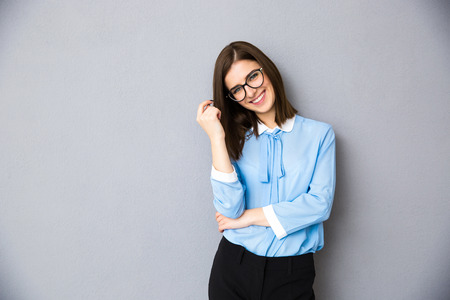 회색 배경 위에 서있는 안경에 웃는 사업가. 파란색 셔츠와 안경 착용. 카메라를 찾고