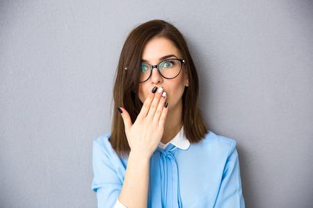 사업가 그녀의 손으로 그녀의 입 취재. 파란색 셔츠와 안경 착용. 회색 배경 위에 서. 카메라를 찾고